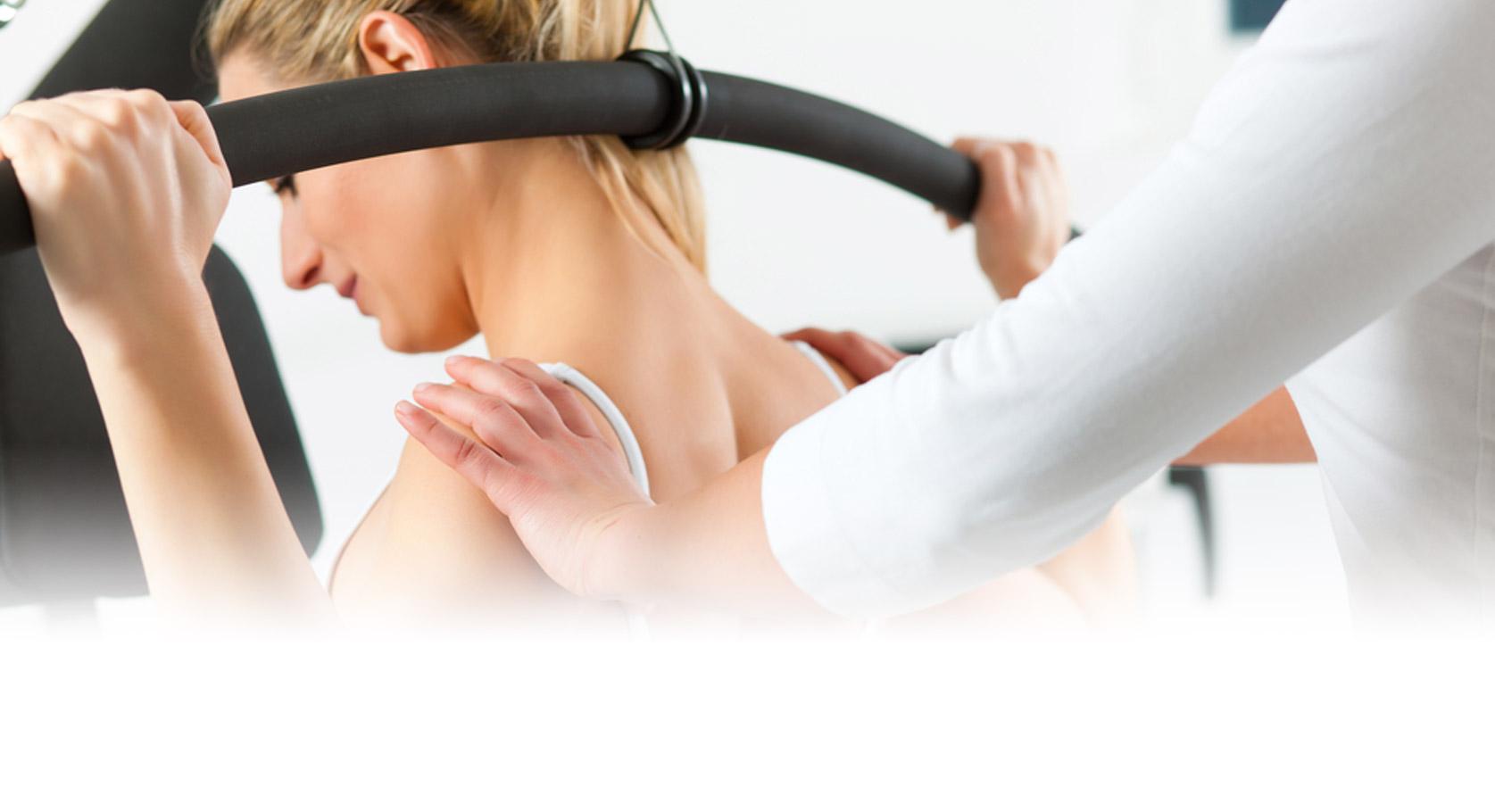 Dame som bruker treningsapparat med hjelp av fysioterapeut
